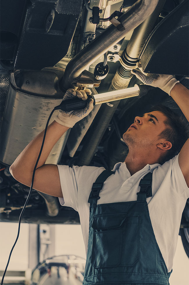 Mechanic looking under a vehicle - MOT and Servicing Leighton Buzzard.